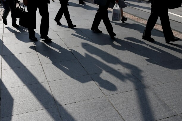 Morning commuters cast shadows on a sidewalk in Tokyo, Japan, on Monday, May 14, 2018. Japan is scheduled to release its first-quarter gross domestic product (GDP) figures on May 16.
