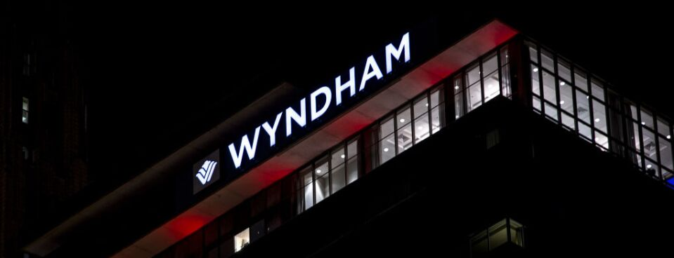 Signage is illuminated at night on the top of a Wyndham hotel.