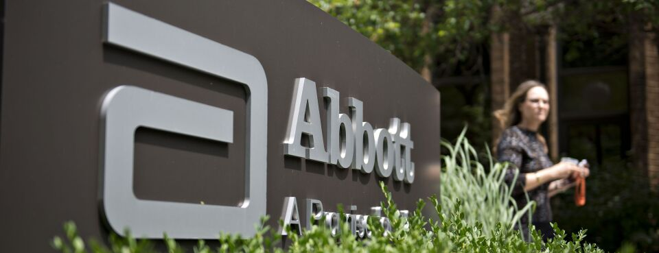 Photo of an employee walking near an Abbott Laboratories sign at the company's headquarters complex in Abbott Park, Ill.