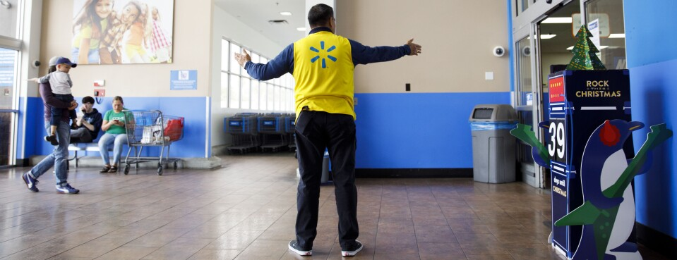 An employee welcomes customers at a Wal-Mart Store.