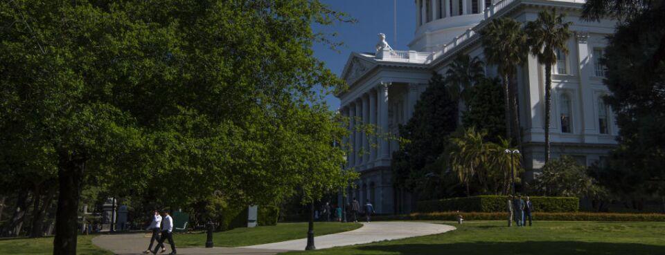 Pedestrians walk past the California State Capitol building in Sacramento, California, U.S., on Thursday, March 30, 2017.
