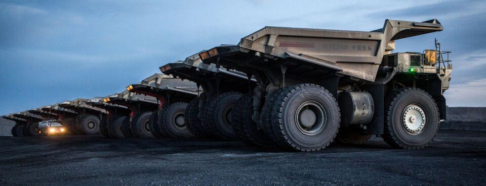 Dump trucks sit parked at a coal deposit.