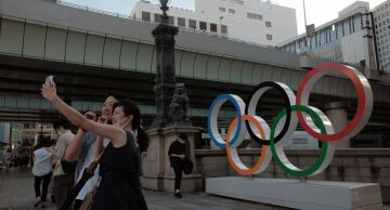 Photo of visitors taking a selfie photograph in front of Olympic rings installed in the Nihonbashi district of Tokyo.