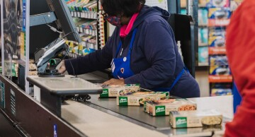 Cashier wearing a heart-embroidered apron checks out a customer at the Kroger Marketplace in Versailles, Kentucky, on Nov. 24, 2020.