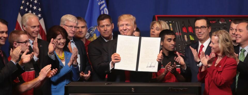 President Donald Trump signs an executive order to revamp the H-1B visa guestworker program during a visit to Kenosha, Wis., on April 18, 2017.