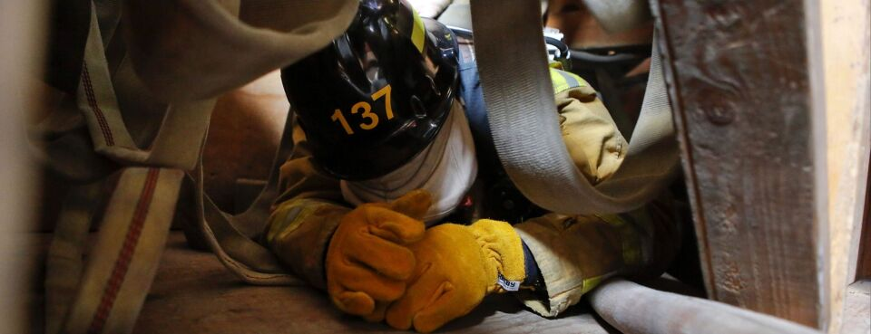 Photo of a fire academy recruit navigating confined spaces during training at the El Camino Community College Fire Academy in Inglewood, Calif.