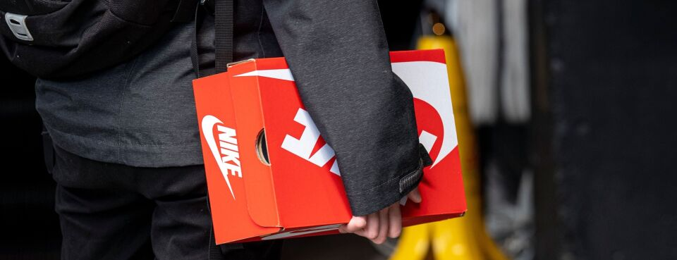 Photo of a person carrying a Nike Inc. branded shoe box while entering a store in San Francisco.