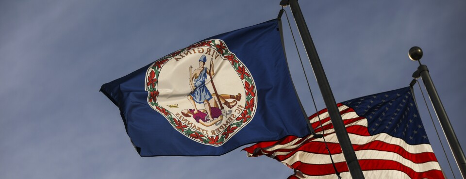 The Virginia state flag and the American flag fly near the Virginia State Capitol, in Richmond.