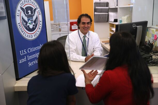 A U.S. Citizenship and Immigration Services officer interviews applicants.