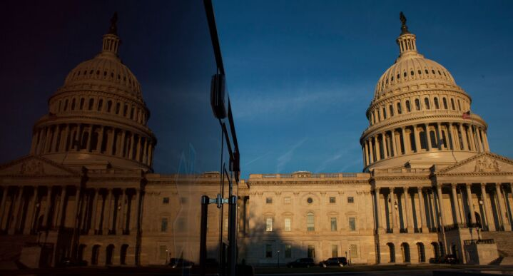 The United States Capitol Building reflects on a truck as the sunrises in Washington, D.C.