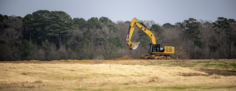 A worker operates a Caterpillar Inc. excavator at a construction site outside of Center, Tex., on Dec. 9, 2019.