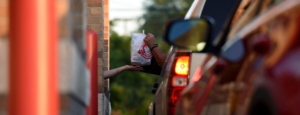 A worker passes an order to a customer in the drive through lane at a Wendy's store.