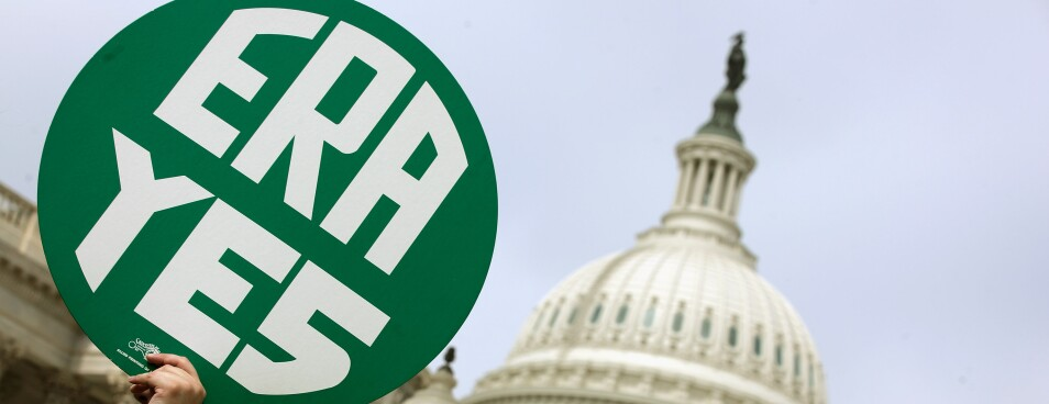 A woman hold up a sign at a rally to mark the congressional passage of the Equal Rights Amendment outside the U.S. Capitol.