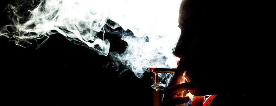 A woman smokes a marijuana cigarette.