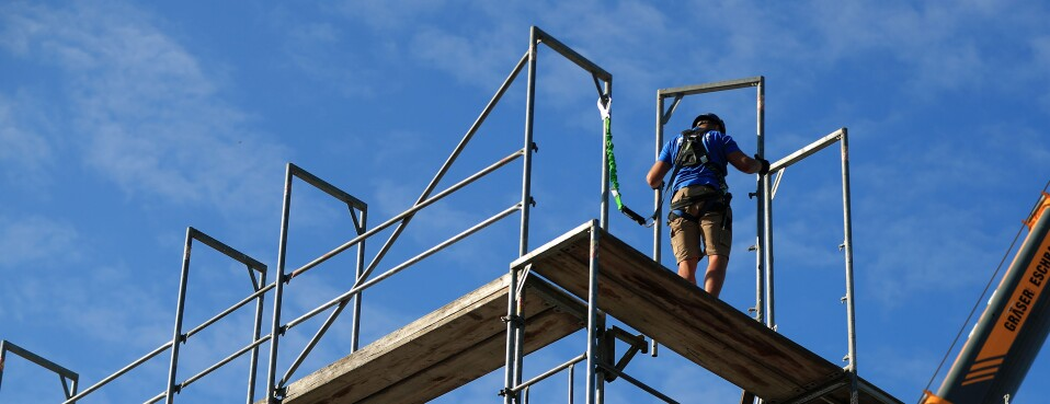 A worker erects scaffolding at a construction site.