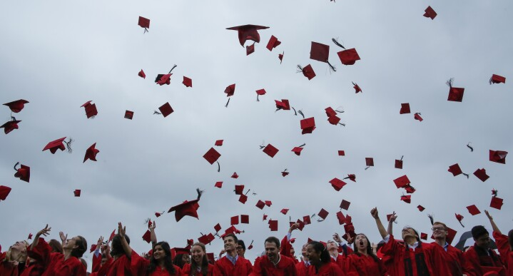 Graduating students toss their hats in the air at the conclusion of their commencement ceremony.