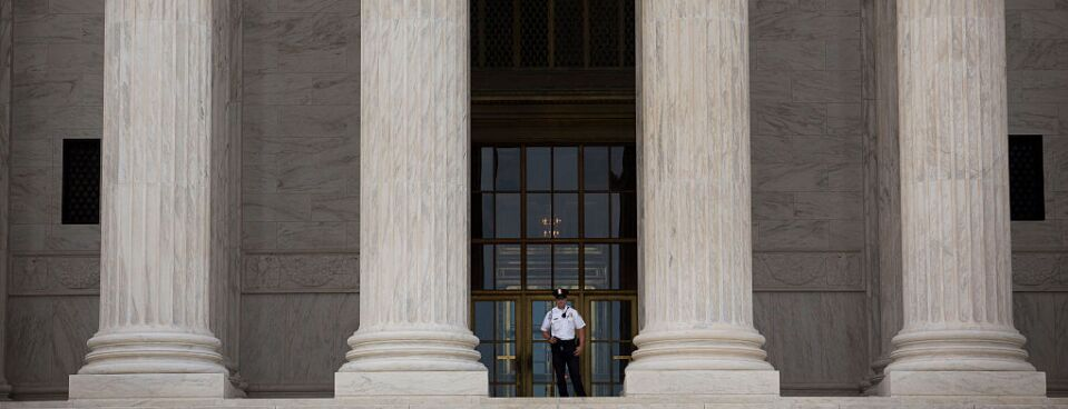 A Supreme Court Police officer stands at the top of the steps at the Supreme Court in Washington, D.C.