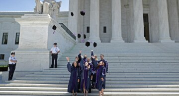 Law School Graduates -- Insights: Georgetown University Law School graduates throw their velvet caps into the air while posing for photographs in front of the U.S. Supreme Court May 20, 2016.