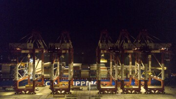 A Cosco Shipping Lines Co. container ship sits moored next to gantry cranes at the Yangshan Deepwater Port, operated by Shanghai International Port Group Co. (SIPG), at night in this aerial photograph taken in Shanghai, China on Wednesday, Jan. 30, 2019. The U.S. and China launched high-level trade talks in Washington with little indication that Beijing will bend to U.S. demands to deepen economic reforms.