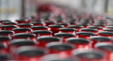 Empty Coca-Cola Classic cans move along a conveyor at a Coca-Cola production facility.