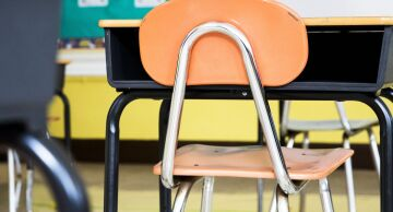 Photo of a school desk and chair in a classroom.