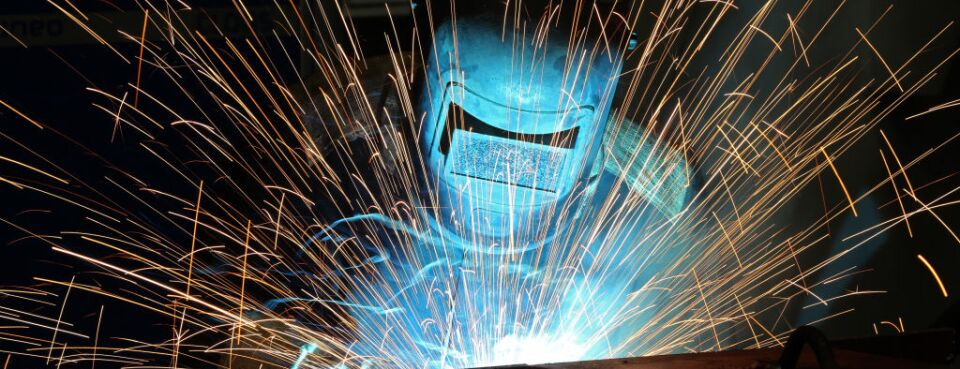 Sparks fly from a welder's arc.