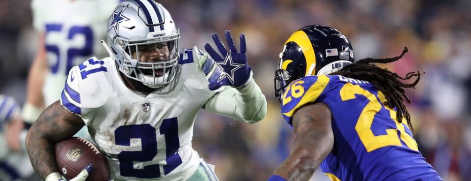 Ezekiel Elliott of the Dallas Cowboys runs with the ball against Mark Barron of the Los Angeles Rams in the NFC Divisional Playoff game at Los Angeles Memorial Coliseum on Jan. 12, in Los Angeles.
