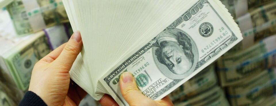 Bank teller holding $100 bills