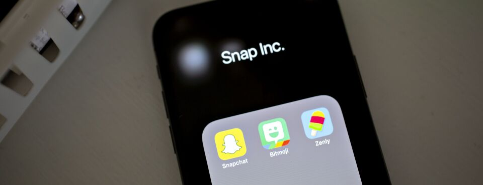 Photo of Snap Inc. Snapchat, Bitmoji, and Zenly application icons displayed on a mobile phone.