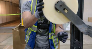 A worker wears a harness while replacing packing tape on a machine.