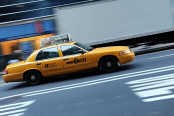 New York yellow cab taxi driving up Fifth Avenue.