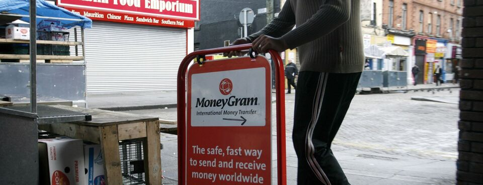 Photo of a shop worker placing a sign for MoneyGram outside his store on Moore Street in Dublin, Ireland.