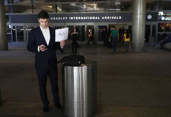 Lawyer holds a sign offering services outside Los Angeles International Airport.