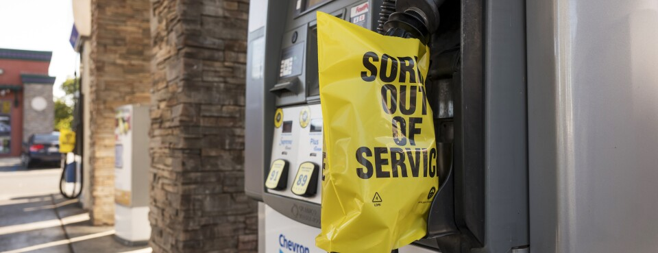 "Plastic covers reading ""Sorry Out Of Service"" are displayed on gas pumps at a gas station during a blackout in northern California."