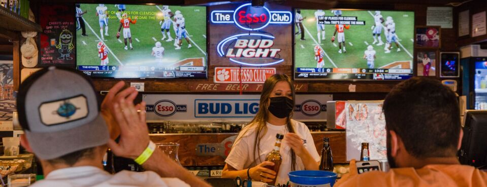 Photo of a bartender serving drinks as customers watch college football at a restaurant in Clemson, S.C.