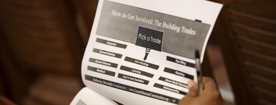 A job seeker reads an information packet during a fair for construction jobs.