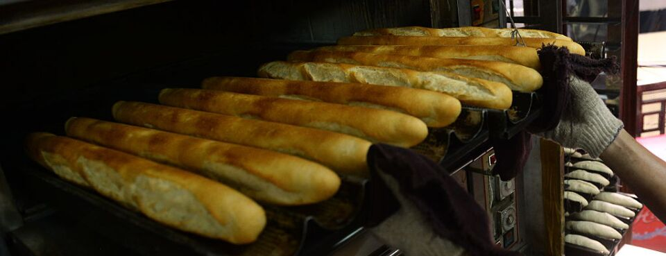 Worker pulls a tray of baked baguettes out of an oven.