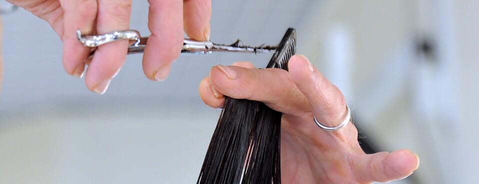 Hairdresser cuts a woman's hair.