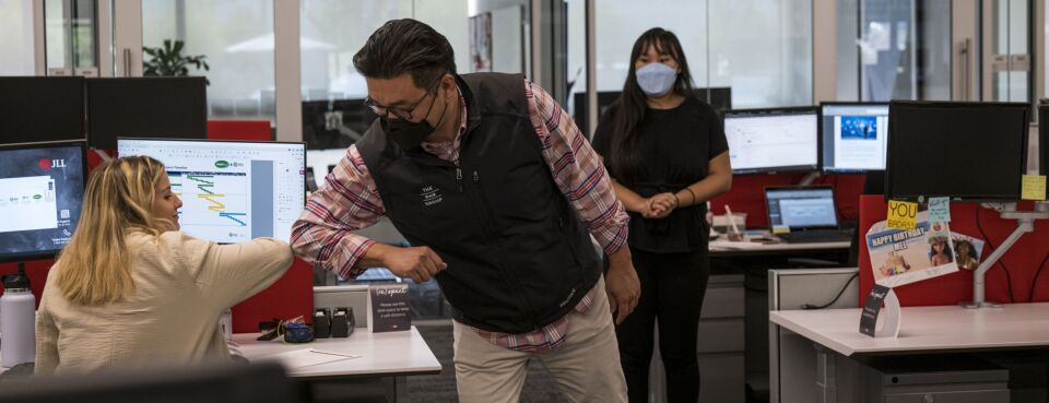 Covid office - Insights: Employees wearing protective masks elbow bump at a JLL office in Menlo Park, Calif., on Sept. 15, 2020.