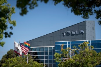 """Tesla Builds Giant Tent To Meet Model 3 Production Targets  Flags fly outside of a Tesla Inc. building in Fremont, California, U.S., on Wednesday, June 20, 2018. Tesla CEO Elon Musk said the company needed another general assembly line to reach its production targets for the Model 3 vehicle. """"A new building was impossible, so we built a giant tent in 2 weeks,"""" Musk said on Twitter."""