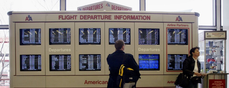 Airline passengers check flight schedules.