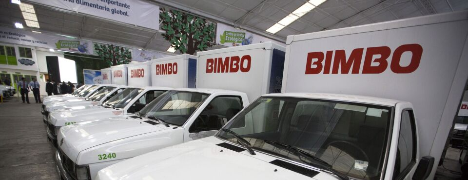 Electric delivery trucks sit inside a Grupo Bimbo sales center.